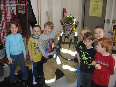 firefighter kneeling with kids